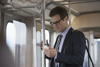 A working day. Businessman in a work suit and tie in a train carriage, checking his phone.