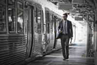A working day. Businessman in a work suit and tie walking on the platform by a train carriage.