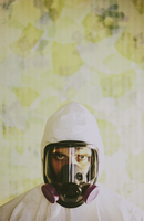 Portrait of a man wearing breathing apparatus and a protective clean suit with a covered head.