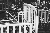Empty hospital bed frames, stacked up in a pile in an empty room.