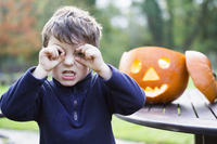 A boy looking through his curved fingers beside a carved pumpkin lantern,