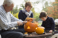 Two adults and a small child with large pumpkins, creating pumpkin lanterns for Halloween.