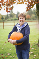 A woman outdoors holding a large orange pumpkin.