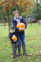 A mature woman and a small boy holding pumpkins, large and small.