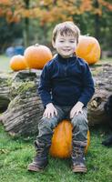 A boy sitting on a large orange pumpkin at pumpkin harvest.