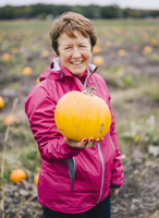 A mature woman in a red jacket, holding out a large orange pumpkin.
