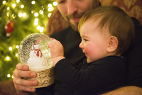 A family at home on Christmas Day. A father and baby daughter looking at a snowglobe.