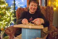 A family at home on Christmas Day. A mature woman opening a stack of presents.