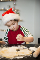 A boy in a Santa hat making Christmas biscuits, cutting out shapes.  11093008459| 写真素材・ストックフォト・画像・イラスト素材|アマナイメージズ
