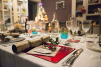 A table laid for a Christmas meal, with silver and crystal glasses and a Christmas tree in the background.