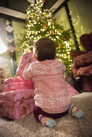 A toddler beside a pile of presents under a Christmas tree.