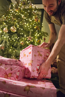A man stacking wrapped presents under the Christmas tree.