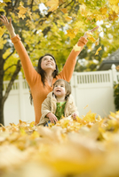 A woman and young child in fallen autumn leaves.