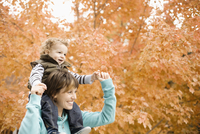 A woman carrying a child on her shoulders, in a woodland in autumn colour.