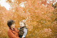 A woman holding a child outdoors surrounded by trees in autumn colour.