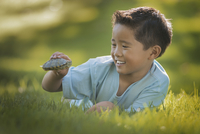 A boy lying on the grass holding a small terrapin or turtle.