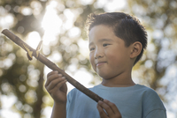 A boy holding a stick with a colourful butterfly perched on it.  11093008622| 写真素材・ストックフォト・画像・イラスト素材|アマナイメージズ