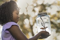 A girl holding a glass jar with a butterfly inside it.  11093008623| 写真素材・ストックフォト・画像・イラスト素材|アマナイメージズ