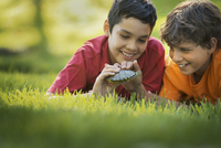 Two boys lying on the grass one holding a terrapin or small turtle.