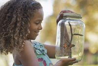 A girl holding a glass jar with a butterfly inside it.  11093008626| 写真素材・ストックフォト・画像・イラスト素材|アマナイメージズ