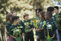 Children in a group learning about plants and flowers, carrying plants and sunflowers.