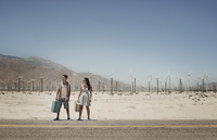 A young couple carrying suitcases, standing by the roadside,  by a wind farm in open country.