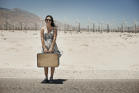A young woman with a suitcase standing on the edge of the highway.