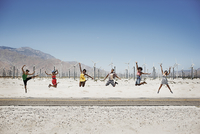 A row of six young people leaping in the air, arms outstretched in wide open space in the desert.