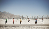 A row of six young people standing arms outstretched by the roadside with a backdrop of wind turbines.