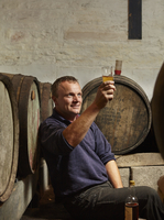 A man sitting among oak barrels at a cider makers, raising a glass and tasting the brew.