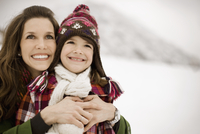 A woman and a child hugging, smiling broadly, in the snowy mountains.