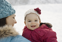 A mother and baby outdoors in the snow.