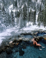 Forest in winter, man sitting in a hot spring.