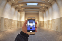 Close up of a hand holding a smart phone, taking a picture of a large room.