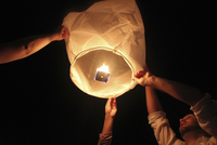 People releasing a Chinese Lantern into the night sky.