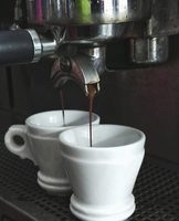 Close up of freshly brewed espresso running into cups from an espresso machine in a coffee shop.