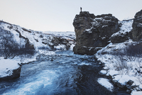Man standing on top of a rock by a river in Iceland in winter.