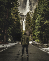 Rear view of a man standing on a path in a forest, a waterfall in the background. 11093009113| 写真素材・ストックフォト・画像・イラスト素材|アマナイメージズ