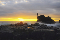 Man standing on a rock by the ocean at sunset.