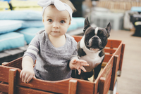 Baby and a French Bulldog sitting in a wooden crate.