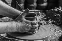 Close up of a potter throwing a pot on a pottery wheel.