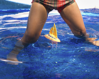 A child playing with a model sail boat in water, legs astride.