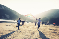 Children flying kites on a sandy beach.