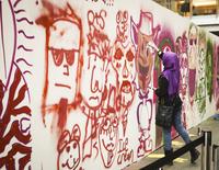 Woman wearing a headscarf, spraying graffiti on a wall.