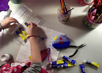 High angle view of a child doing arts and crafts, holding a tube of paint.