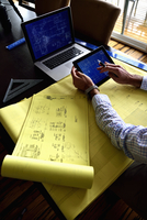 High angle view of an architect working on a technical drawing, using a digital tablet.