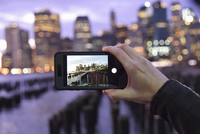 Person holding a smart phone, taking a photograph of a city skyline in the evening.