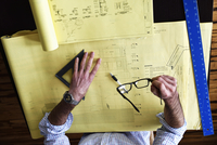 High angle view of an architect working on a technical drawing.