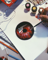 High angle view of a person painting a red flower with a fine paintbrush.