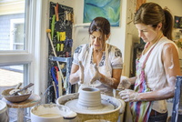 Two women at a pottery class, standing in front of a pottery wheel.